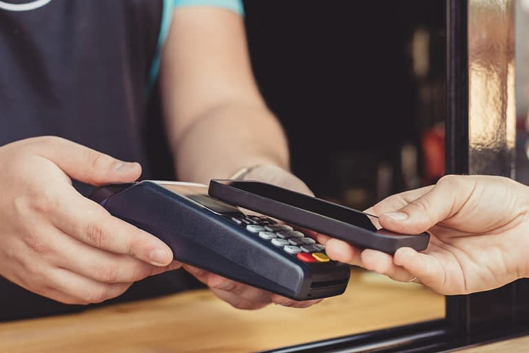 person paying pay through smartphone using nfc 2021 09 01 21 09 05 utc 1260x840 1
